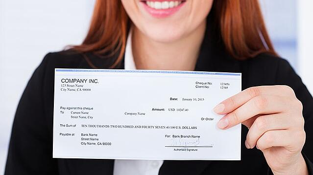 woman holding payroll check