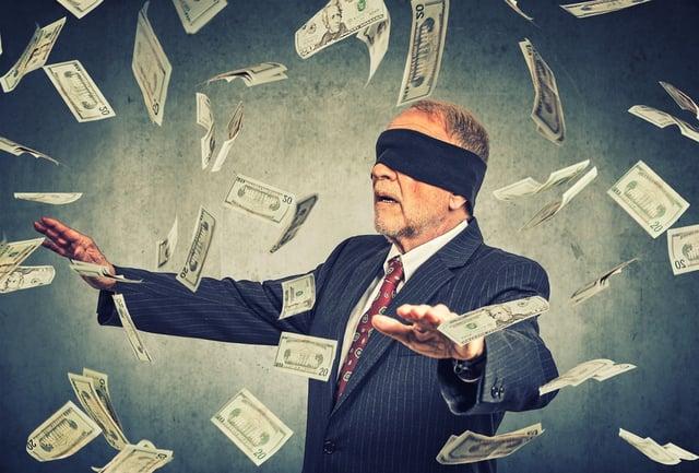Blindfolded businessman trying to catch dollar bills.jpeg